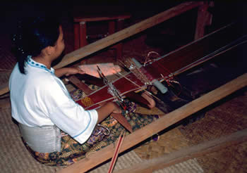 Young Iban woman weaving a ceremonial headband